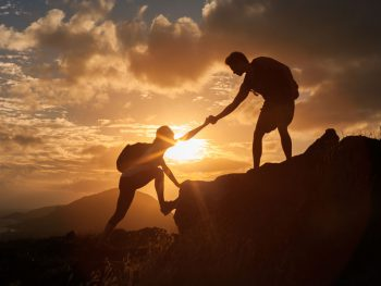 Vancouver area life coach, person helping another person up mountain